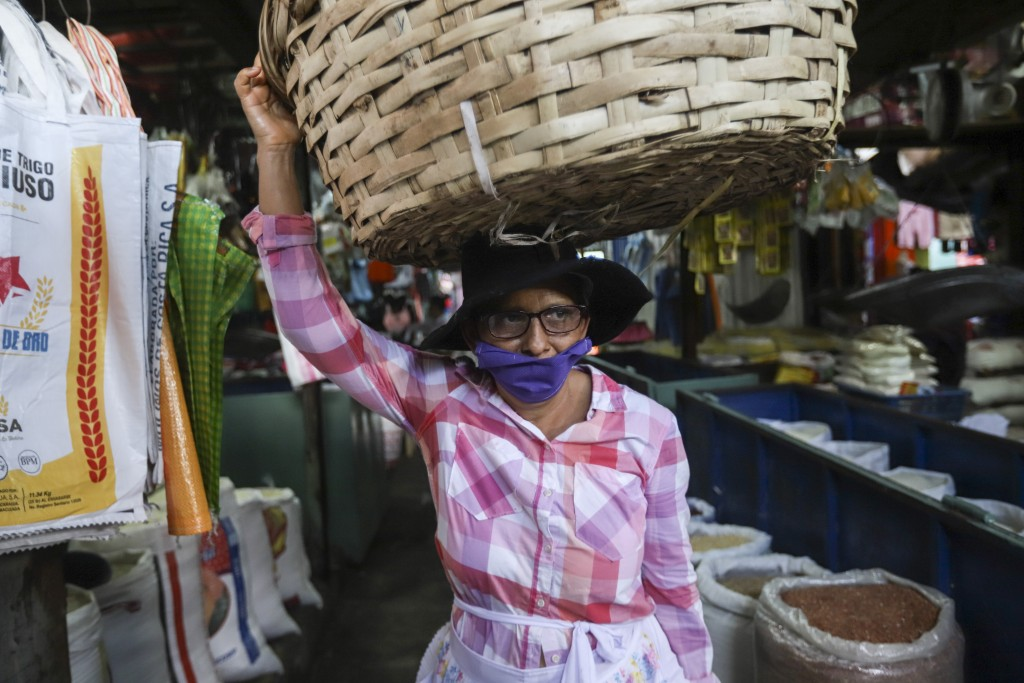 A fruit vendor, wearing a protective face mask, makes her way through a popular market in Managua, Nicaragua, Tuesday, April 7, 2020. Restaurants are ...