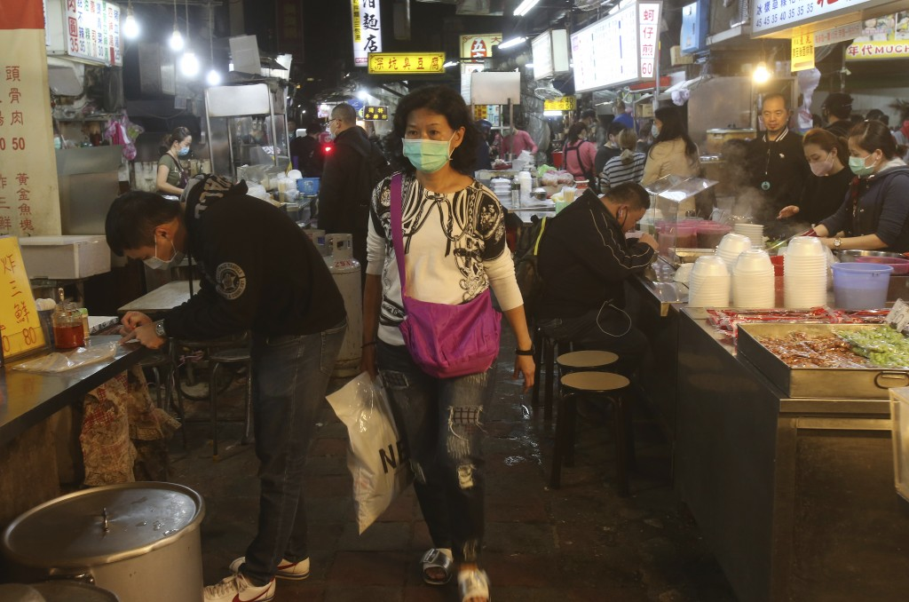 People wear face masks to help curb against the spread of the coronavirus and visit at a night market in Taipei, Taiwan, Wednesday, April 8, 2020. The...