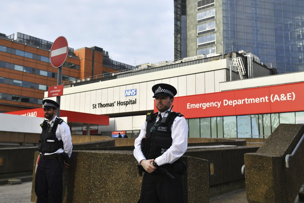 Police officers stand outside St Thomas' Hospital in the background in central London, where Prime Minister Boris Johnson remains in intensive care as...