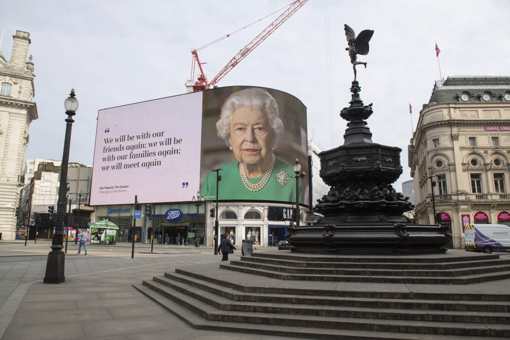 An image of Queen Elizabeth II and quotes from her historic TV broadcast commenting on the coronavirus epidemic are displayed at Piccadilly Circus in ...