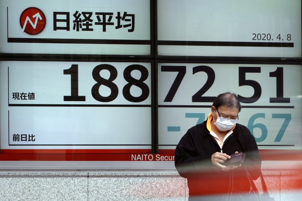 A man stands in front of an electronic stock board showing Japan's Nikkei 225 index at a securities firm Wednesday, April 8, 2020, in Tokyo. Asian sha...