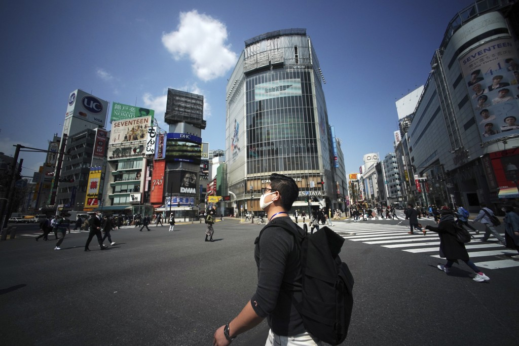 Fewer than usual people at Shibuya Scramble Crossing is seen Wednesday, April 8, 2020, in Tokyo. Japanese Prime Minister Shinzo Abe declared a state o...