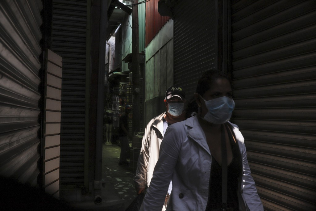 People, wearing protective face masks, make their way through a popular market in Managua, Nicaragua, Tuesday, April 7, 2020. Restaurants are empty, t...