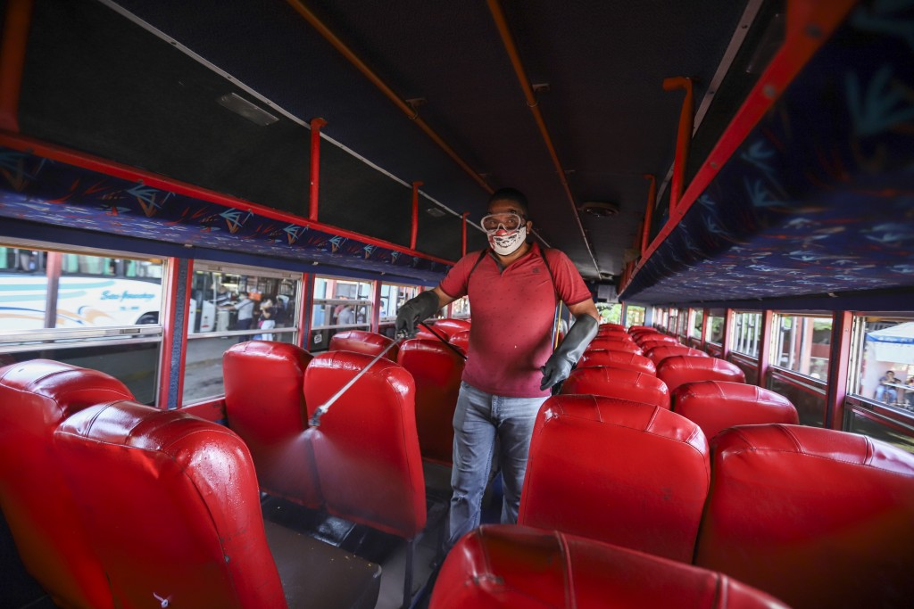 A man disinfects a bus to prevent the spread of the new coronavirus, at the Mayoreo market in Managua, Nicaragua, Tuesday, April 7, 2020. Restaurants ...