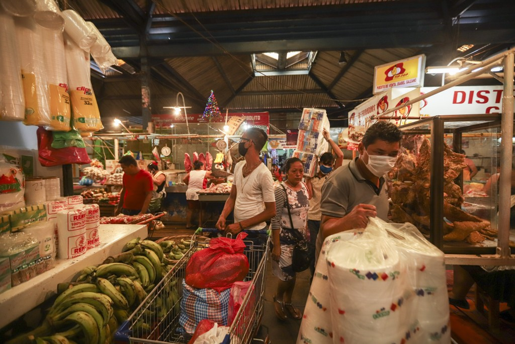 Customers, some wearing protective face masks, shop at a popular market in Managua, Nicaragua, Tuesday, April 7, 2020. Restaurants are empty, there's ...