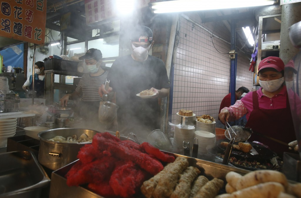 Vendors wear face masks to help curb the spread of the coronavirus and serve for customers at a night market in Taipei, Taiwan, Wednesday, April 8, 20...