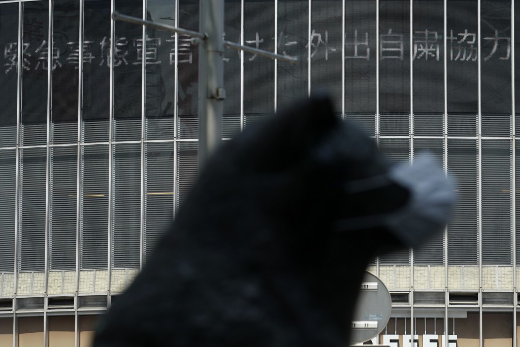 An electronic news bulletin board shows the message of cooperation of self-restraint following state of emergency, near a statue of a Japanese Akita d...