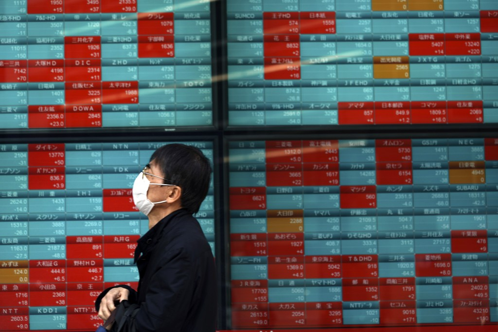 A man walks past an electronic stock board showing Japan's Nikkei 225 index at a securities firm Wednesday, April 8, 2020, in Tokyo. Asian shares were...