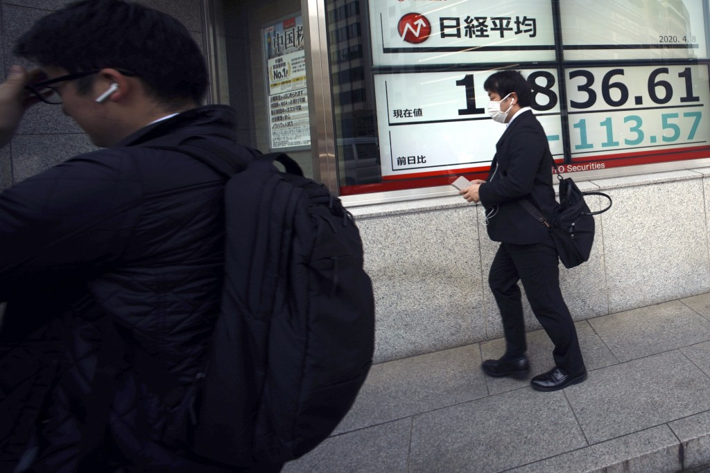 Men walk past an electronic stock board showing Japan's Nikkei 225 index at a securities firm Wednesday, April 8, 2020, in Tokyo. Asian shares were mo...
