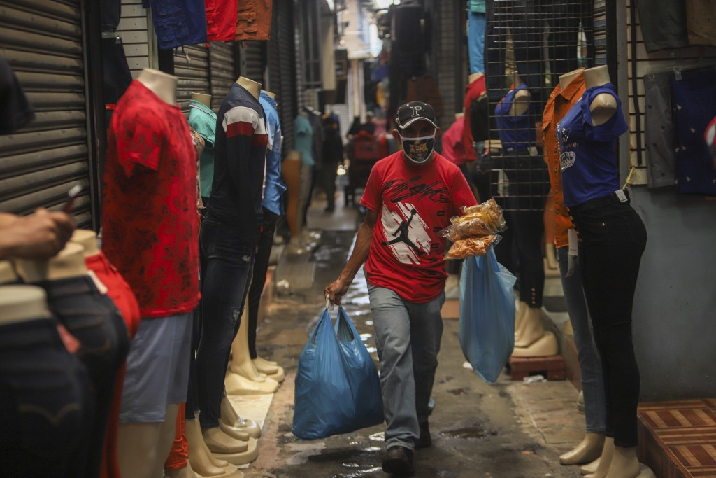 A man, wearing a protective face mask, walks through a popular market in Managua, Nicaragua, Tuesday, April 7, 2020. Restaurants are empty, there's li...