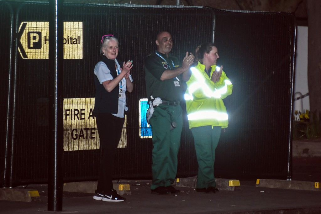 Members of the National Health Service applaude outside St Thomas' Hospital in central London as British Prime Minister Boris Johnson was moved to int...