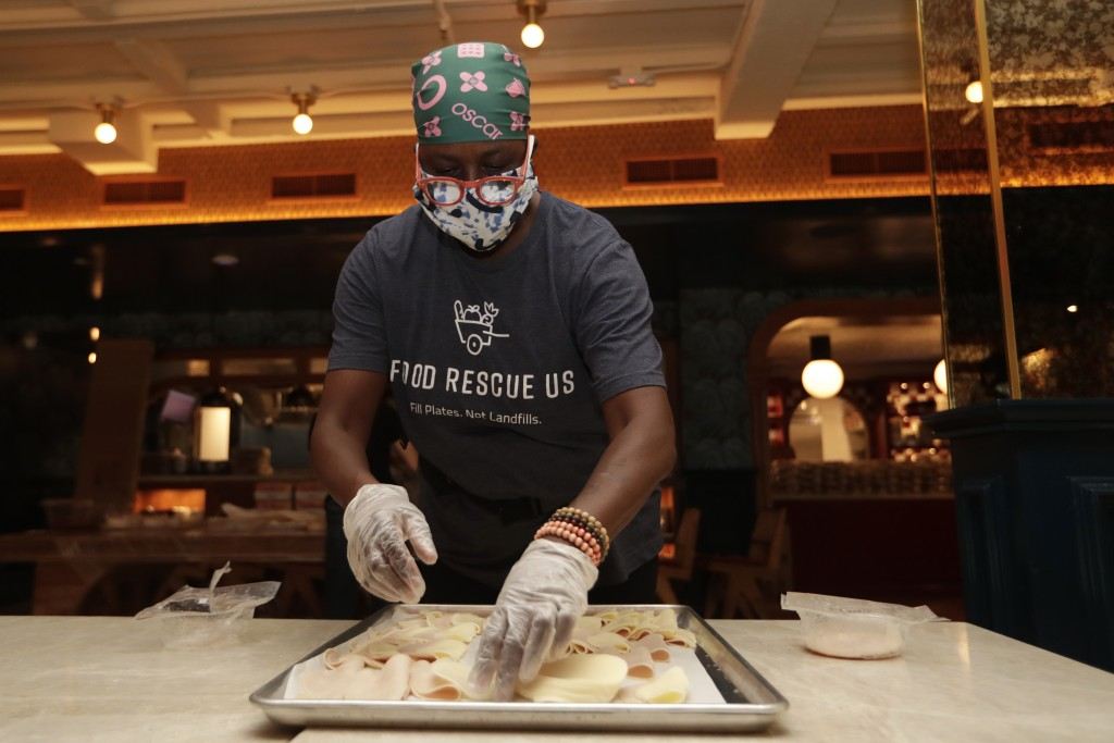 Sharon Holm, a volunteer from Food Rescue US, prepares cold cuts for sandwiches at Marcus Samuelsson's Red Rooster Restaurant during the new coronavir...