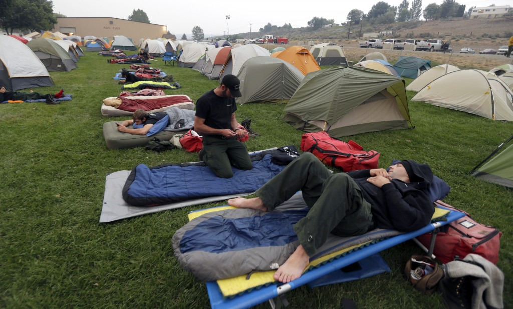 FILE - In this Aug. 25, 2015, file photo, firefighters rest at a camp near the Okanogan Complex Fire in Okanogan, Wash. The outbreak of the coronaviru...