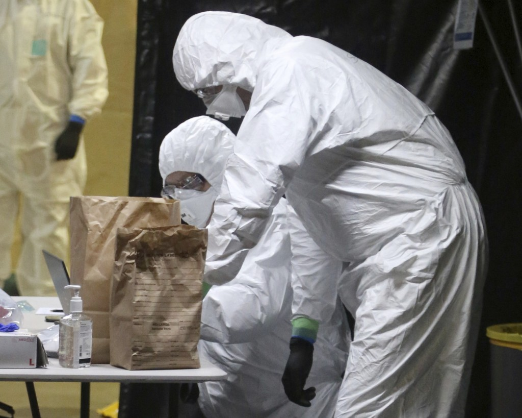 In this Wednesday, April 8, 2020, photo provided by the New South Wales Police, investigators in protective gear examine material from the Ruby Prince...