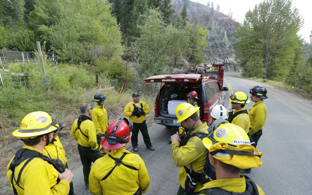 FILE - In this Aug. 21, 2015, file photo, firefighters from several King County agencies gather for a briefing while fighting a wildfire near Twisp, W...