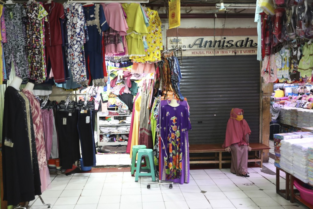 A clothes seller waits for costumers at a quiet market in Jakarta, Indonesia, Friday, April 10, 2020. Authorities began stricter measures to halt the ...