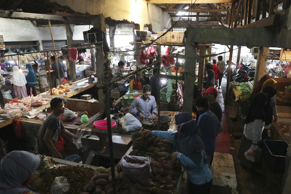 People buy vegetables at a traditional market in Jakarta, Indonesia, Friday, April 10, 2020. Authorities began stricter measures to halt the new coron...