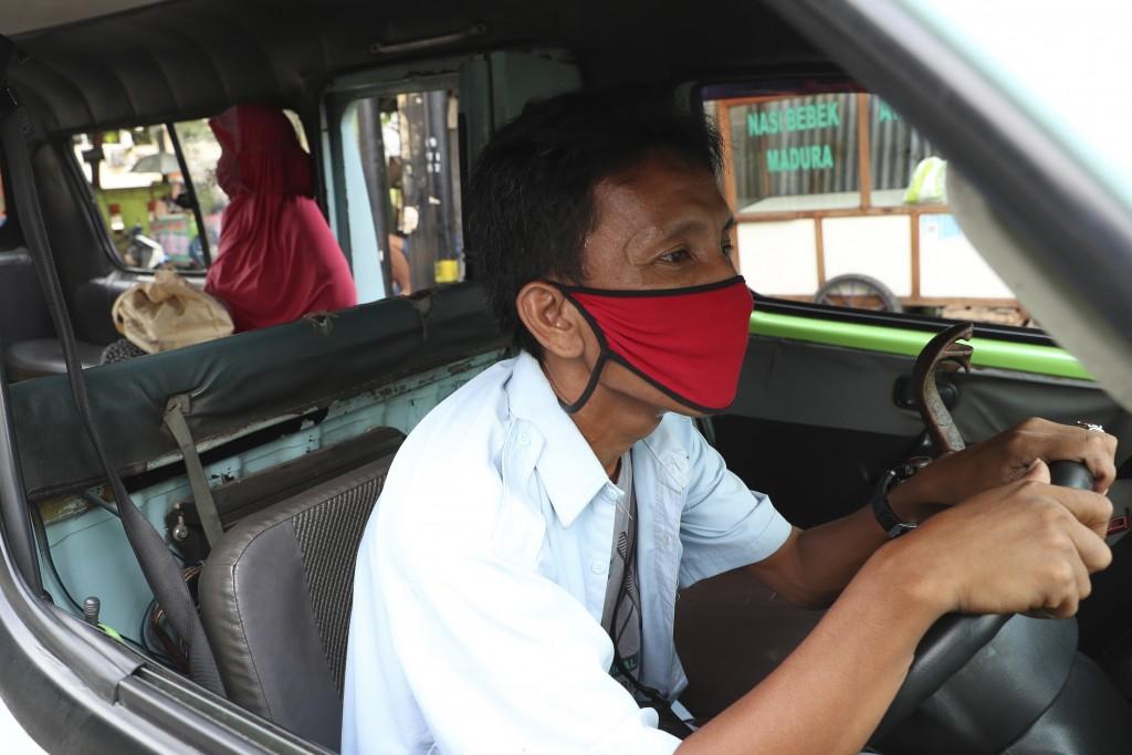 A minivan driver waits for passengers in Jakarta, Indonesia, Friday, April 10, 2020. Authorities began stricter measures to halt the new coronavirus' ...