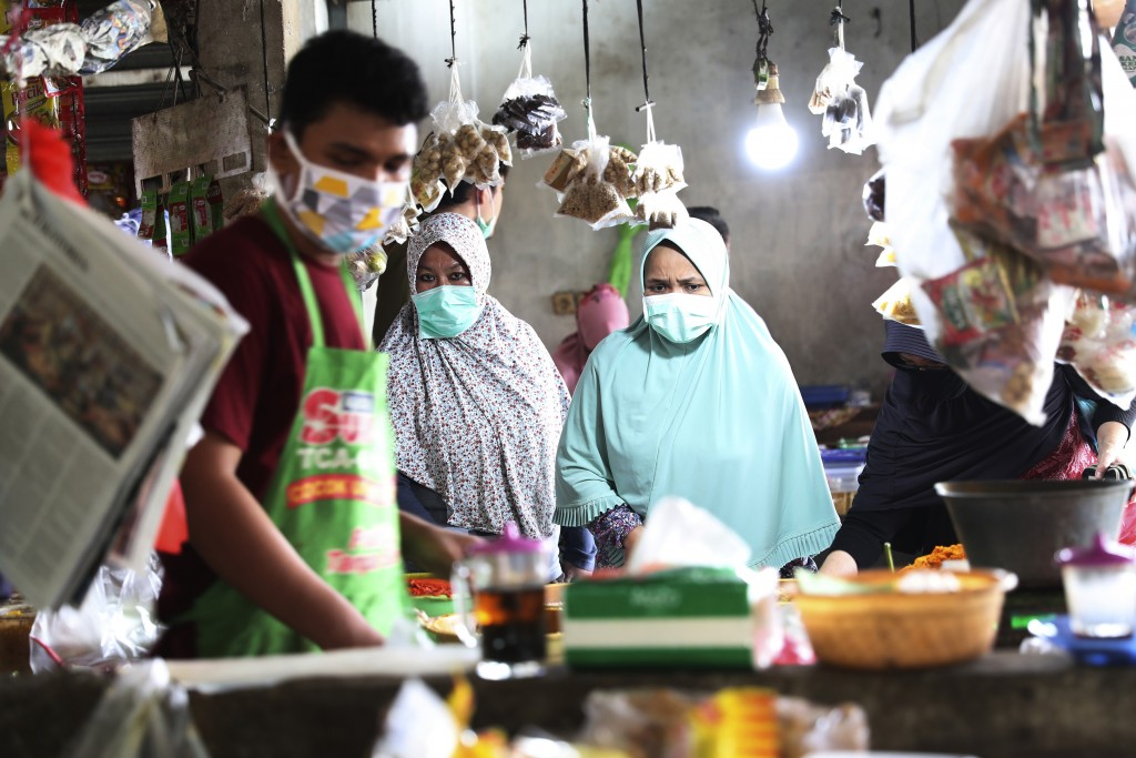 People wear masks at a traditional market in Jakarta, Indonesia, Friday, April 10, 2020. Authorities began stricter measures to halt the new coronavir...
