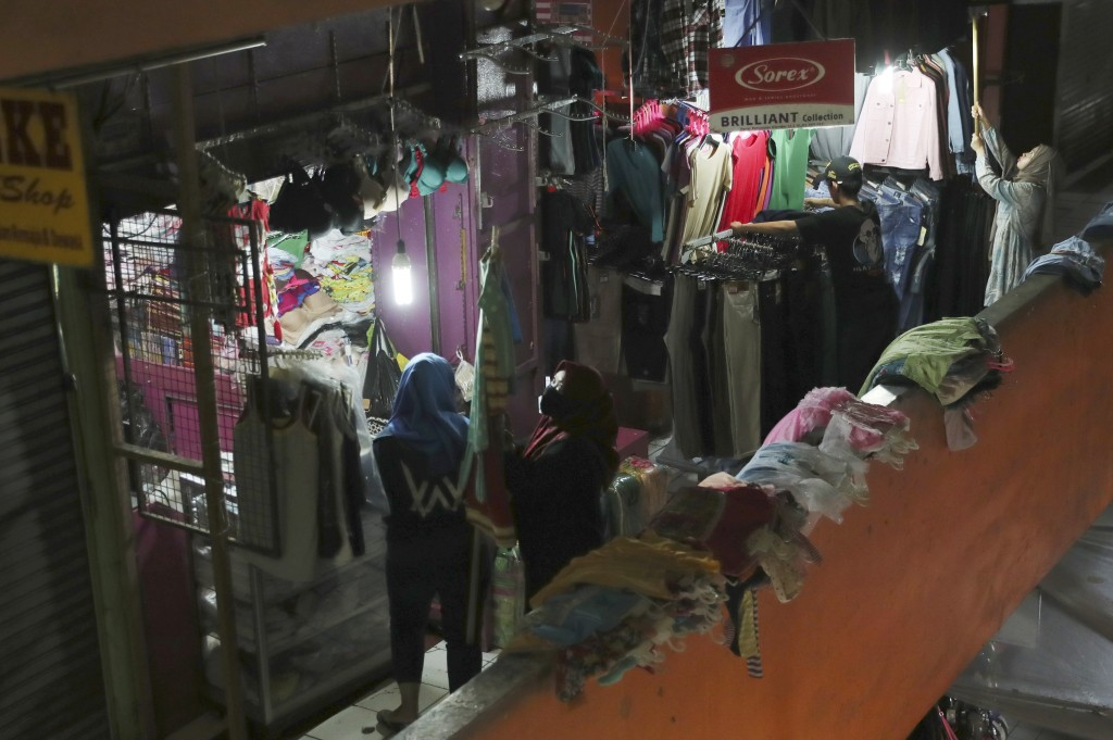 Clothes sellers prepare to open their shops at a quiet market in Jakarta, Indonesia, Friday, April 10, 2020. Authorities began stricter measures to ha...