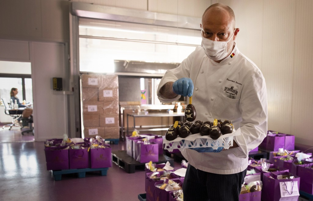 One of Belgium's top chocolate producers Dominique Persoone, wearing a face mask to protect against coronavirus, displays one of his chocolate Easter ...