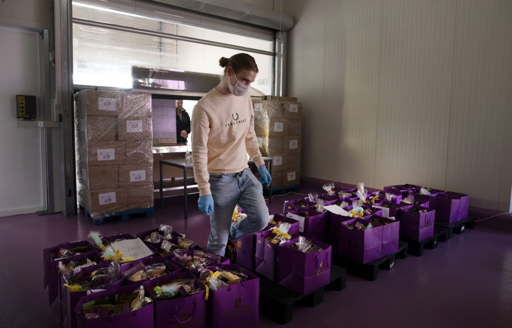 A worker picks orders among bags of chocolate to deliver to a client waiting at a makeshift window at the Chocolate Line warehouse of Dominique Persoo...