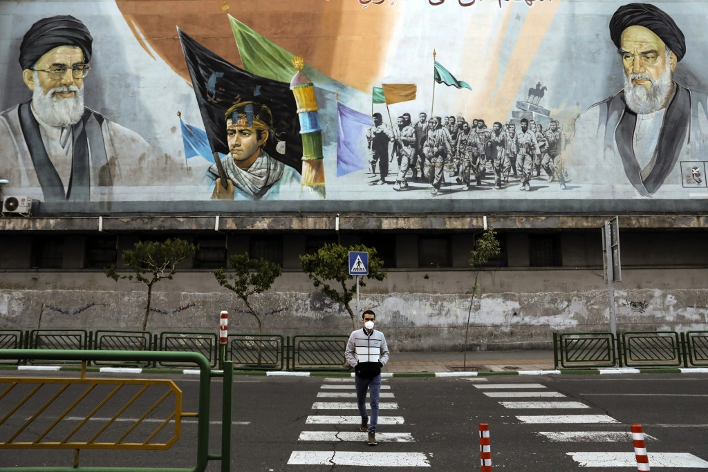 In this Friday, April 3, 2020 photo, a man crosses an empty street under portraits of the late Iranian revolutionary founder Ayatollah Khomeini, right...