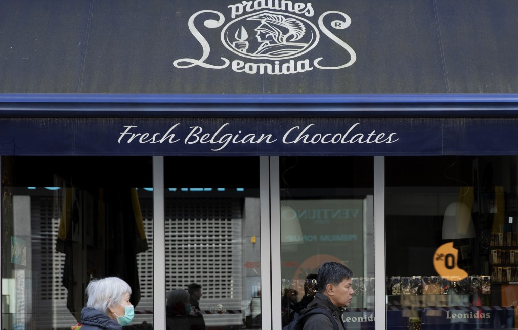 In this photo taken Saturday, March 14, 2020, a woman in a face mask walks by the closed Leonidas chocolate shop in Antwerp, Belgium. As all non-essen...