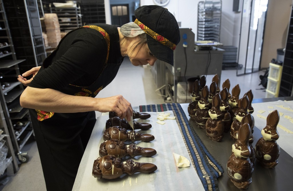 In this photo taken on Wednesday, April 8, 2020, Genevieve Trepant decorates chocolate rabbits at her shop, Cocoatree, in Lonzee, Belgium. As all non-...