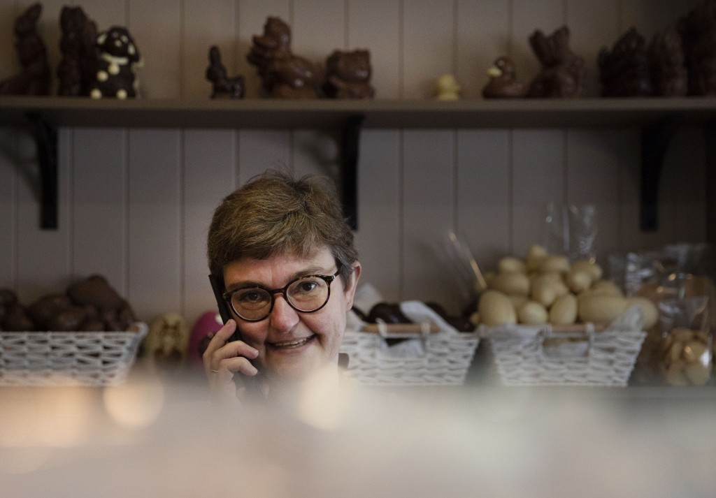 In this photo taken on Wednesday, April 8, 2020, owner of the Praleen chocolate shop Marleen Van Volsem takes orders over the phone at her shop in Hal...