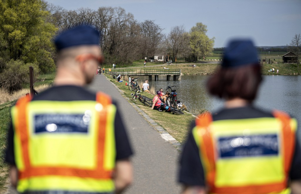 Police officers patrol next to a lake in Budapest, Hungary, Friday, April 12, 2020. The government has extended the lockdown implemented the due to th...