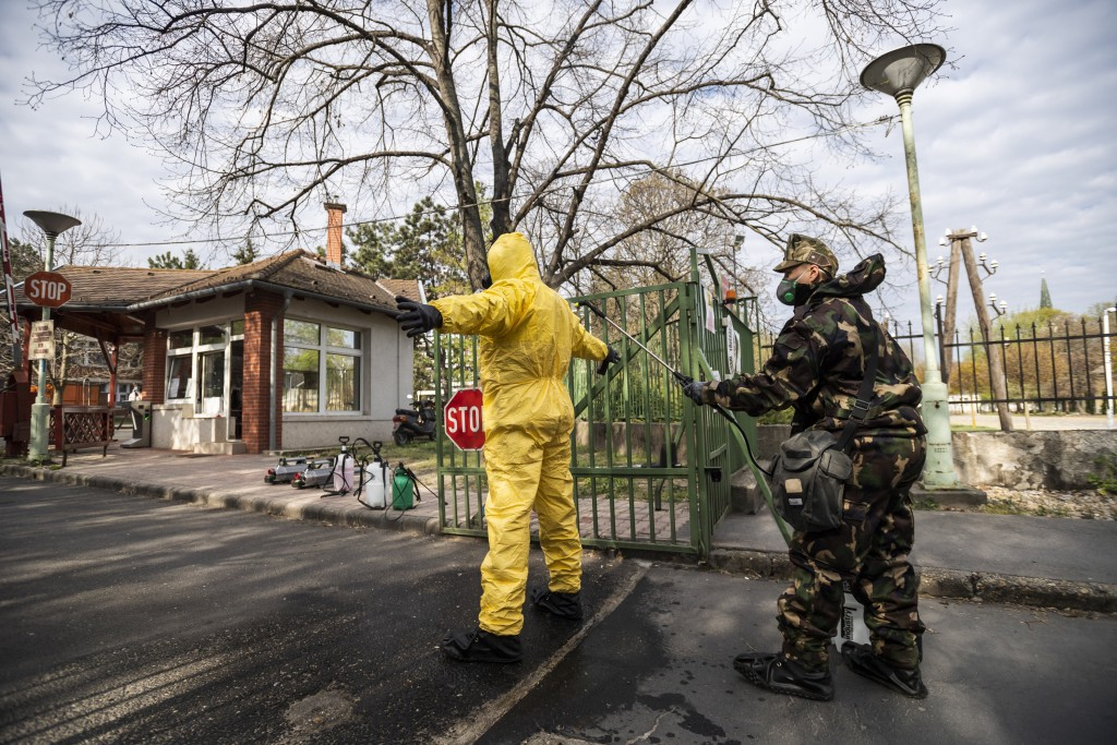 The protective suit of a soldier is disinfected after sanitizing a care home for the elderly where more than 198 people have been infected with the no...
