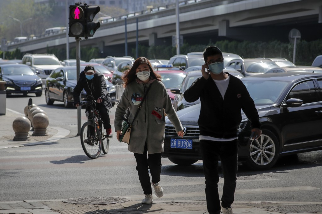 People wearing protective face masks to help prevent the spread of the new coronavirus walk across a street as motorists clog in heavy traffic during ...