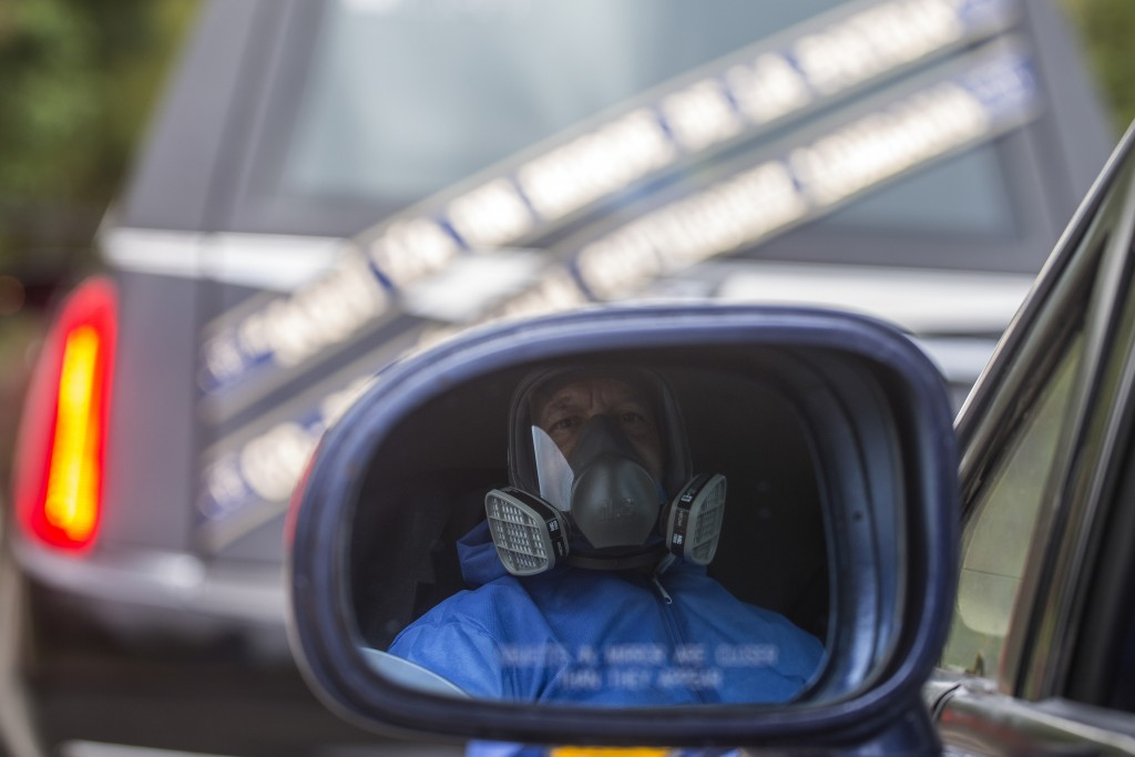 A driver wearing hazardous materials gear sits in a funerary car behind the hearse carrying the body of Dr. William Gutierrez, after arriving for his ...