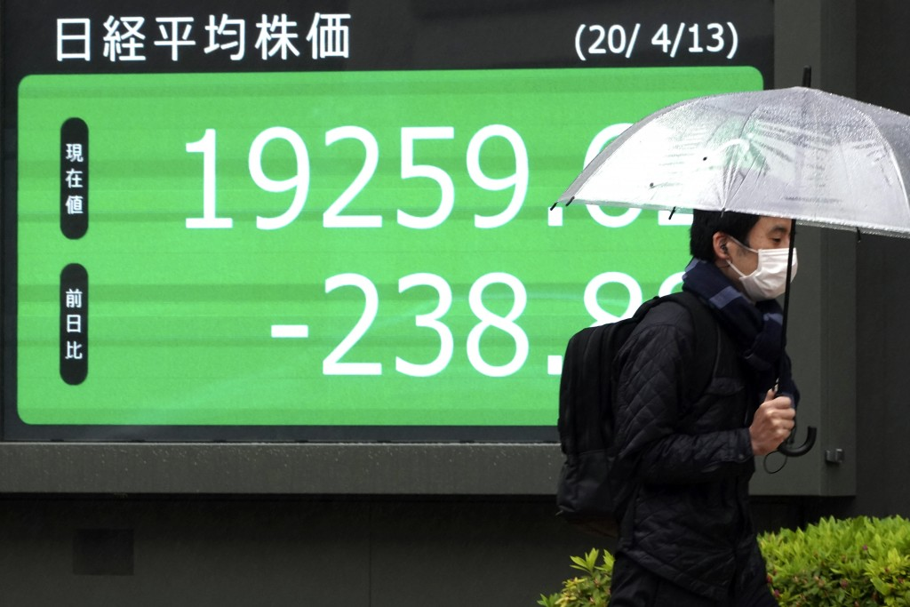 A man with a protective mask walks in the rain past an electronic stock board showing Japan's Nikkei 225 index at a securities firm in Tokyo Monday, A...