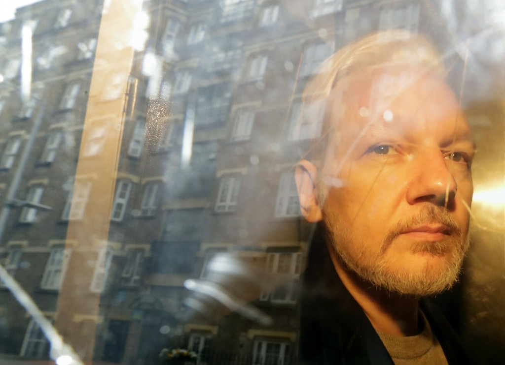 FILE- In this May 1, 2019 file photo, buildings are reflected in the window as WikiLeaks founder Julian Assange is taken from court, where he appeared...