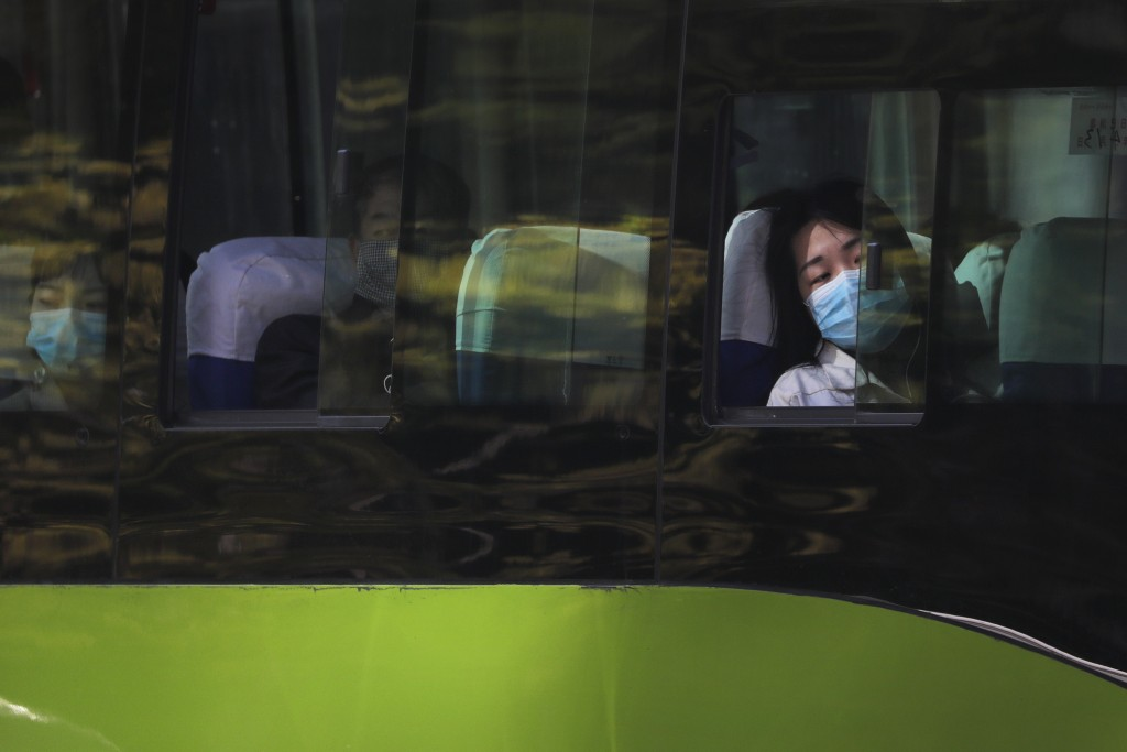 A woman wearing a protective face mask to prevent the spread of the new coronavirus looks out of a window of a bus traveling from the outskirts of the...