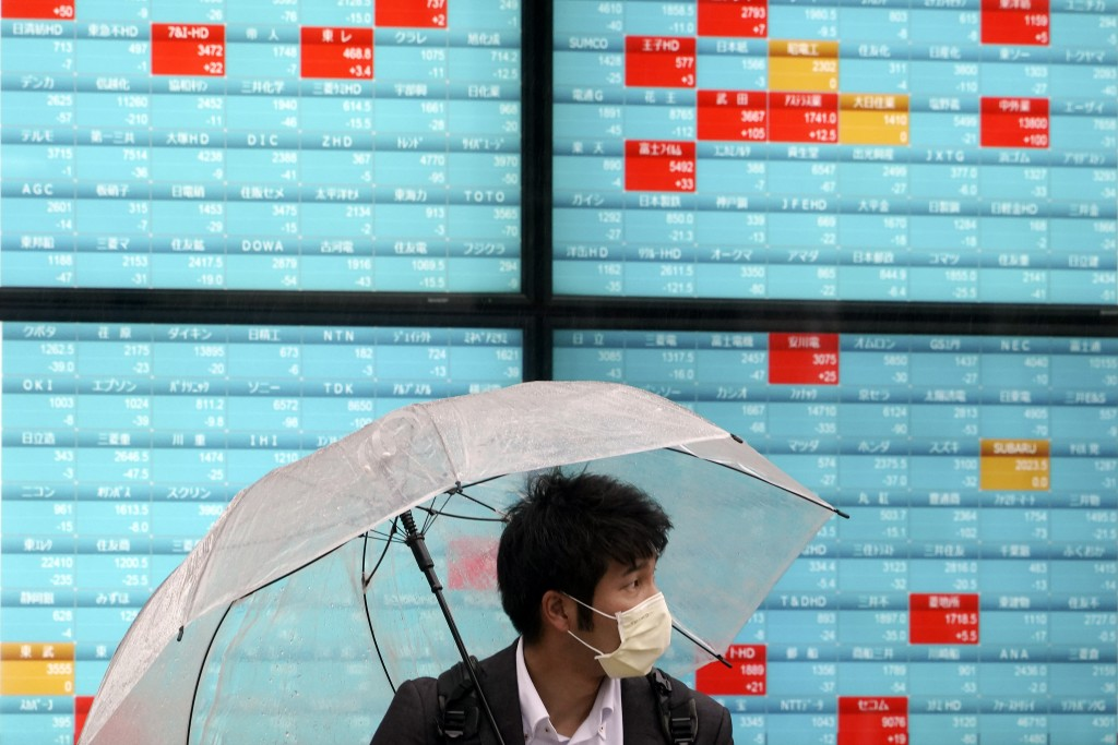 A man with a protective mask stands in the rain in front of an electronic stock board showing Japan's Nikkei 225 index at a securities firm in Tokyo M...