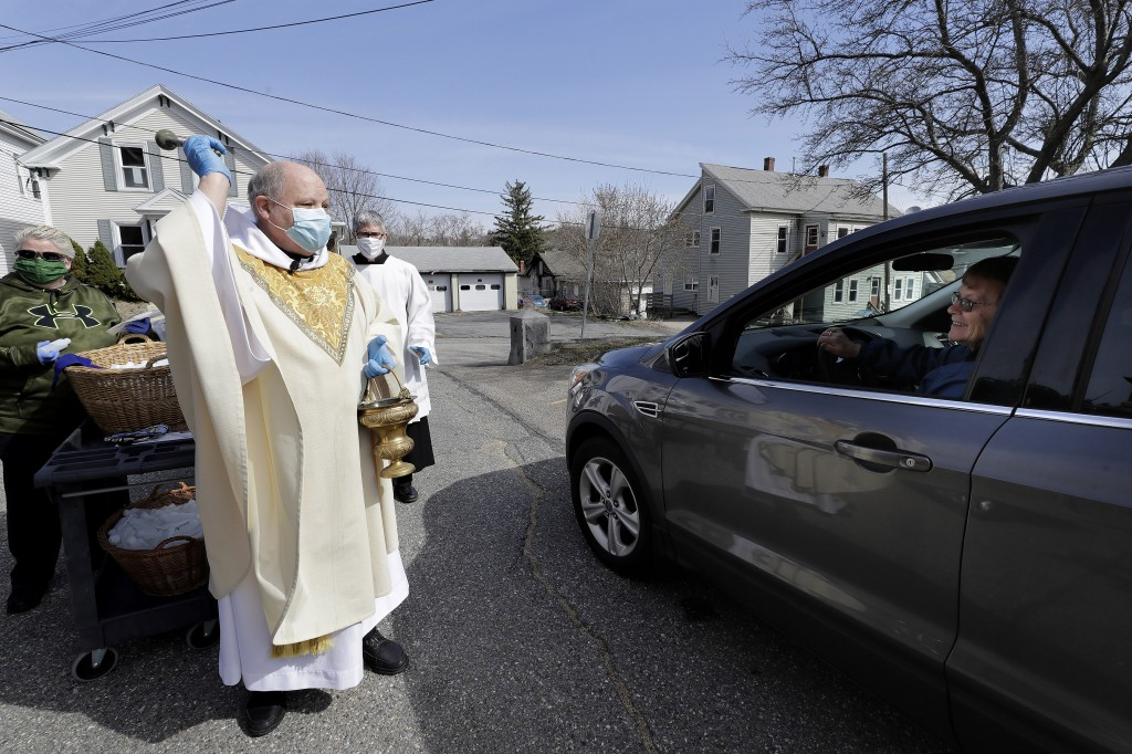 Rev. William Schipper, pastor of Mary, Queen of the Rosary Parish, left, wears a mask and gloves out of concern for the coronavirus as he sprinkles ho...