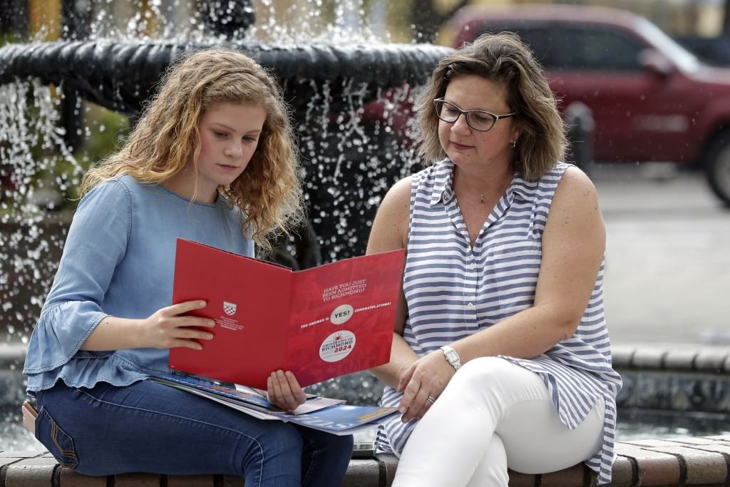 In this Friday, April 10, 2020, photo in Sanford, Fla., Serra Sowers, left, and her mother Ebru Ural look over brochures from various colleges. The co...