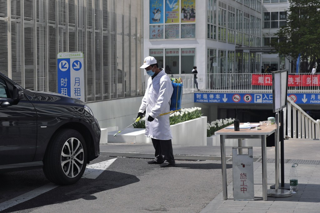A worker wearing a protective face mask to prevent the spread of the new coronavirus sprays disinfectant as a vehicle prepares to enter to an office b...