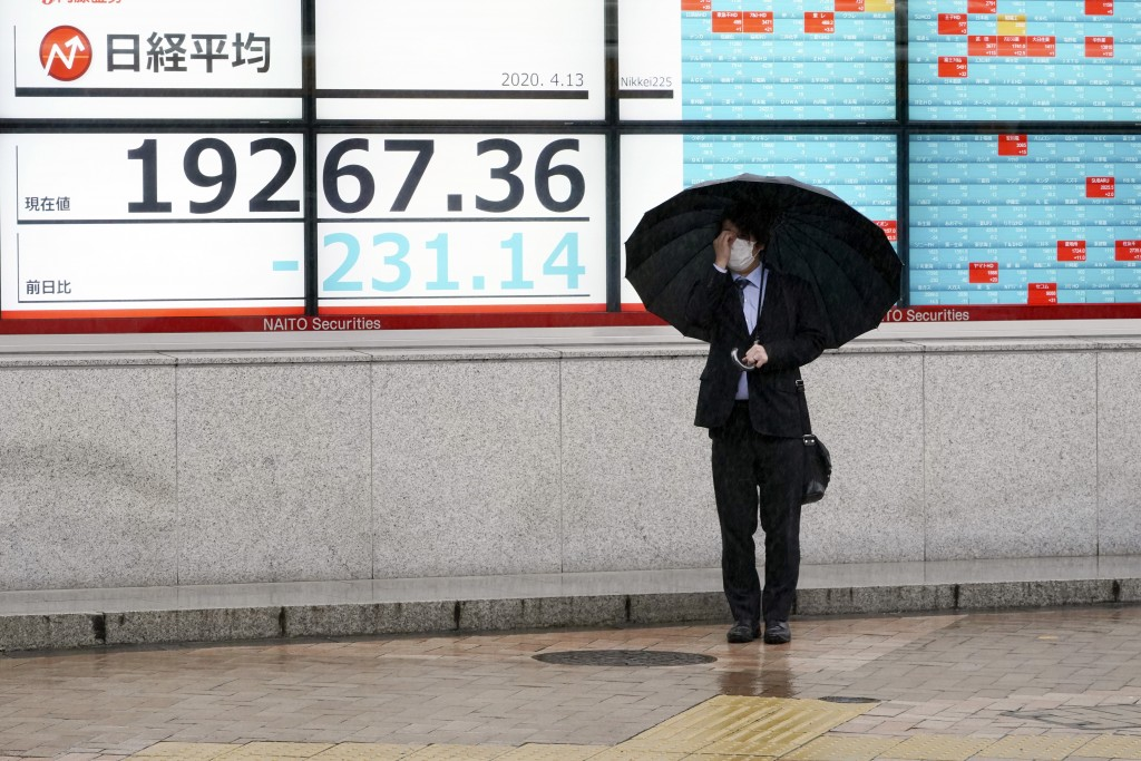 A man wearing a protective mask stands in the rain in front of an electronic stock board showing Japan's Nikkei 225 index at a securities firm in Toky...
