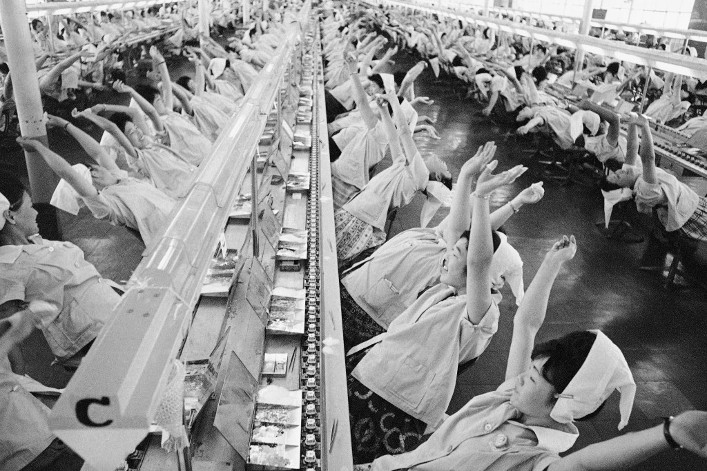 FILE - In this May 7, 1963, file photo, workers along assembly lines at the transistor radio parts maker take a brief break every hour in this unusual...