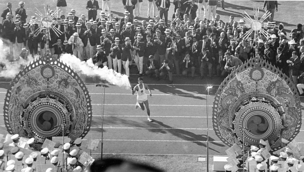 FILE - In this Oct. 10, 1964, file photo, Japanese runner Yoshinori Sakai carries the Olympic Torch during the opening ceremonies of the 1964 Summer O...