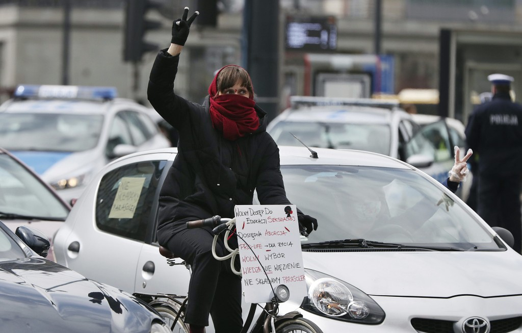 A woman on her bike joins others, self isolated in their cars to protect against coronavirus, take part in a protest against plans for the parliament ...
