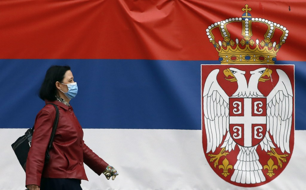 A woman wearing a face mask walks by a Serbian flag placed on a street prior a curfew set up to help prevent the spread of the new coronavirus in Belg...