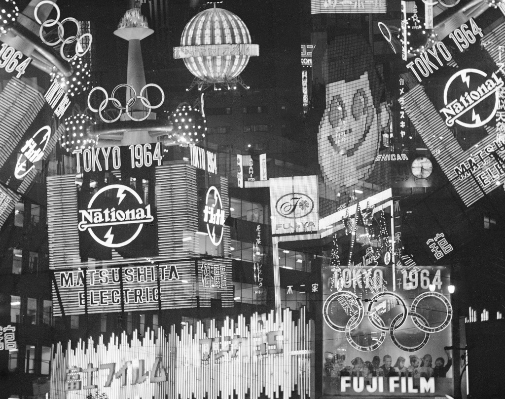 FILE - In this Dec. 16, 1963, file photo, the five-ring Olympics symbols stand out in the jumble of bright lights in downtown Tokyo. The signs dot Tok...