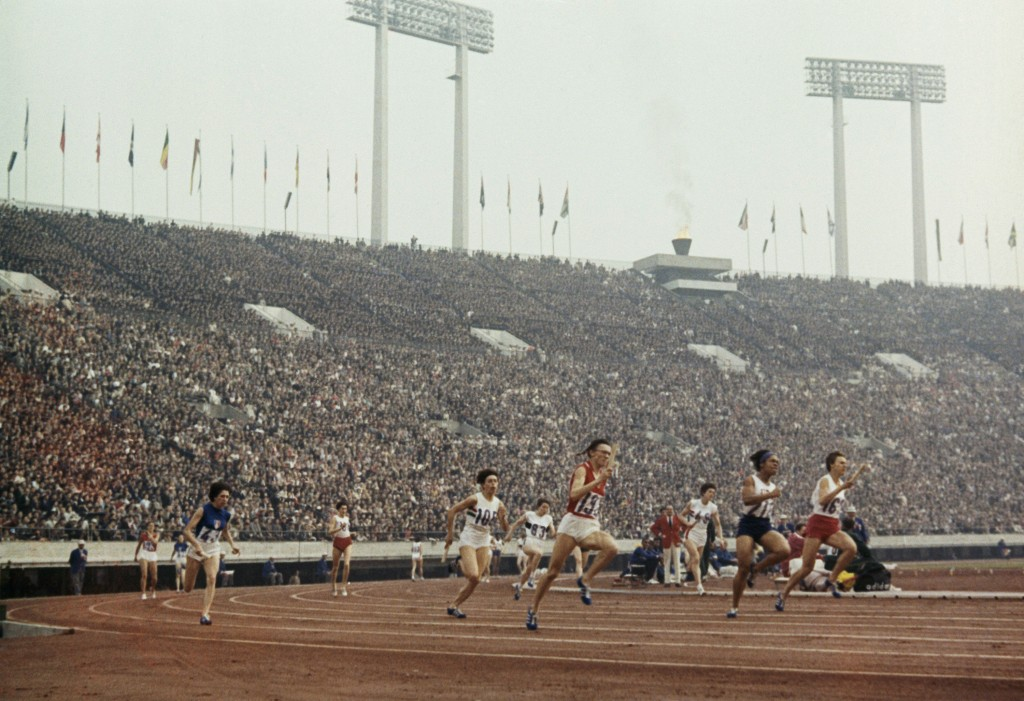 FILE - This Oct. 22, 1964, file photo shows crowds and athletes during running of women's 400-meter relay at the 1964 Tokyo Olympics.  The 1964 Tokyo ...