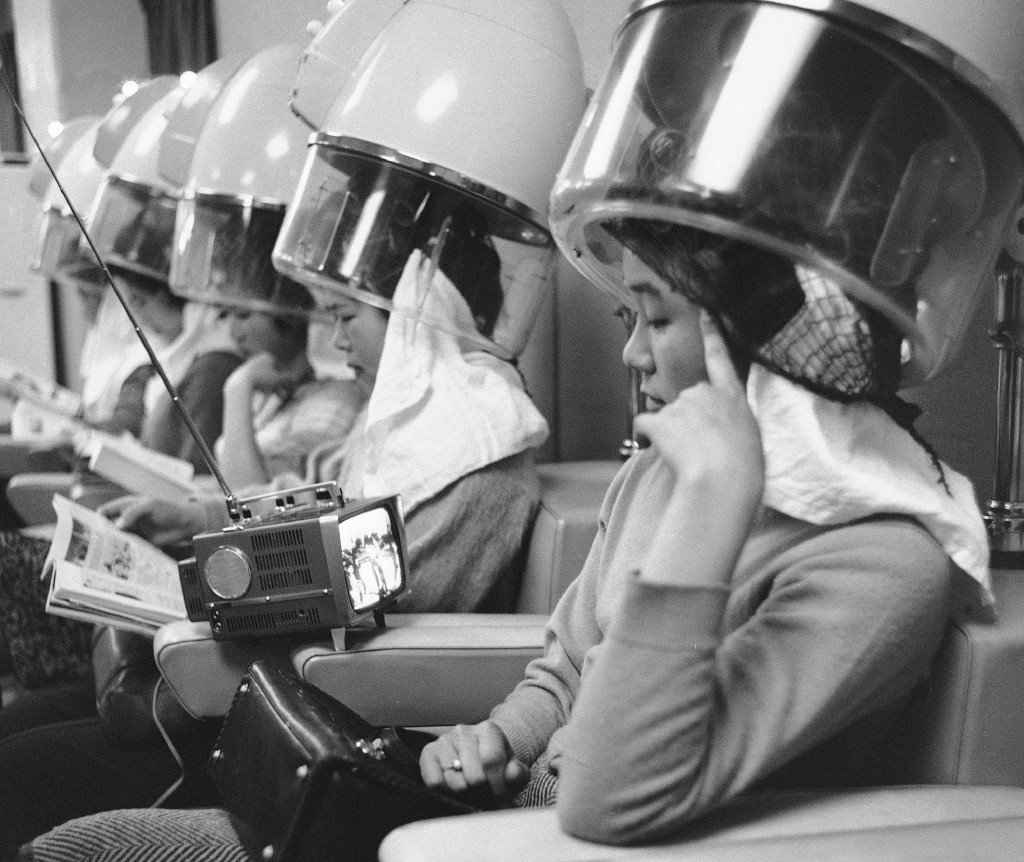 FILE - In this Feb. 21, 1963, file photo, a Tokyo housewife watches a TV program on a tiny set she brought along with her to the hairdressers. The six...