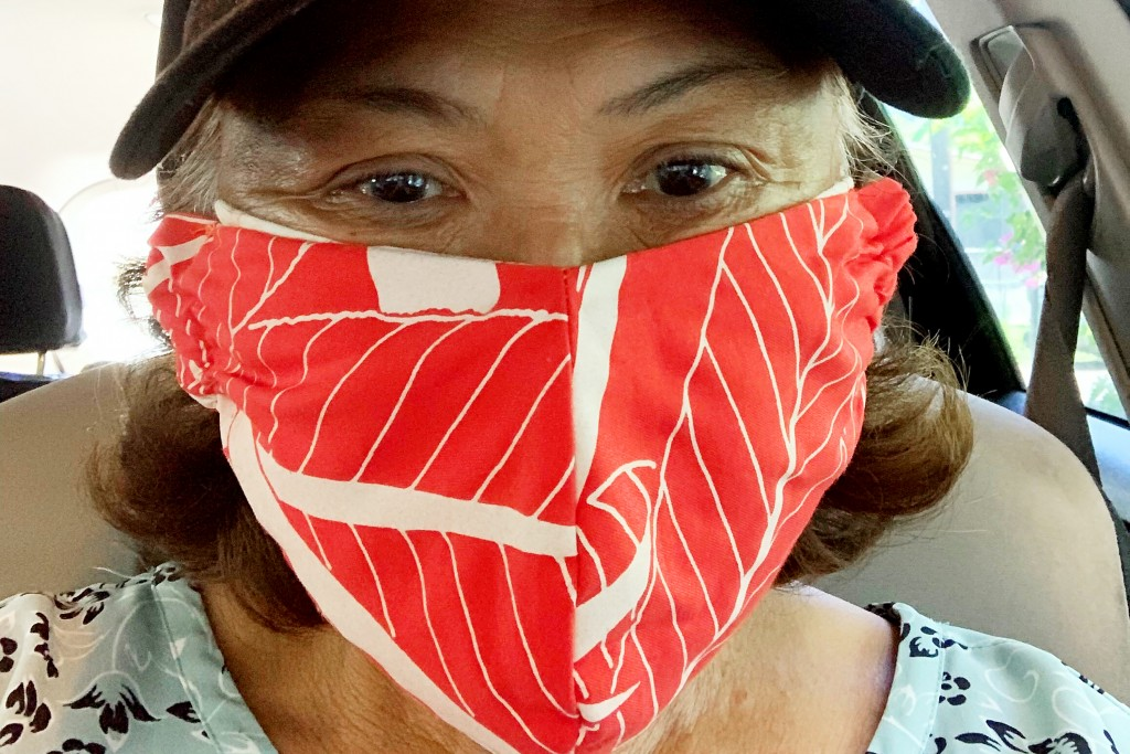 This April 7, 2020 photo provided by Candy Suiso shows her in Makaha, Hawaii, wearing a bird of paradise aloha print mask made by her sister. Face mas...
